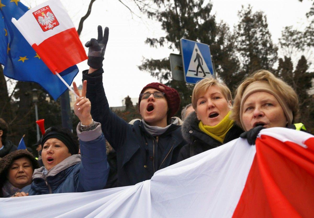 Демонстранты с флагами Польши и Евросоюза выкрикивают лозунги во время акции протеста возле здания парламента в Варшаве / REUTERS