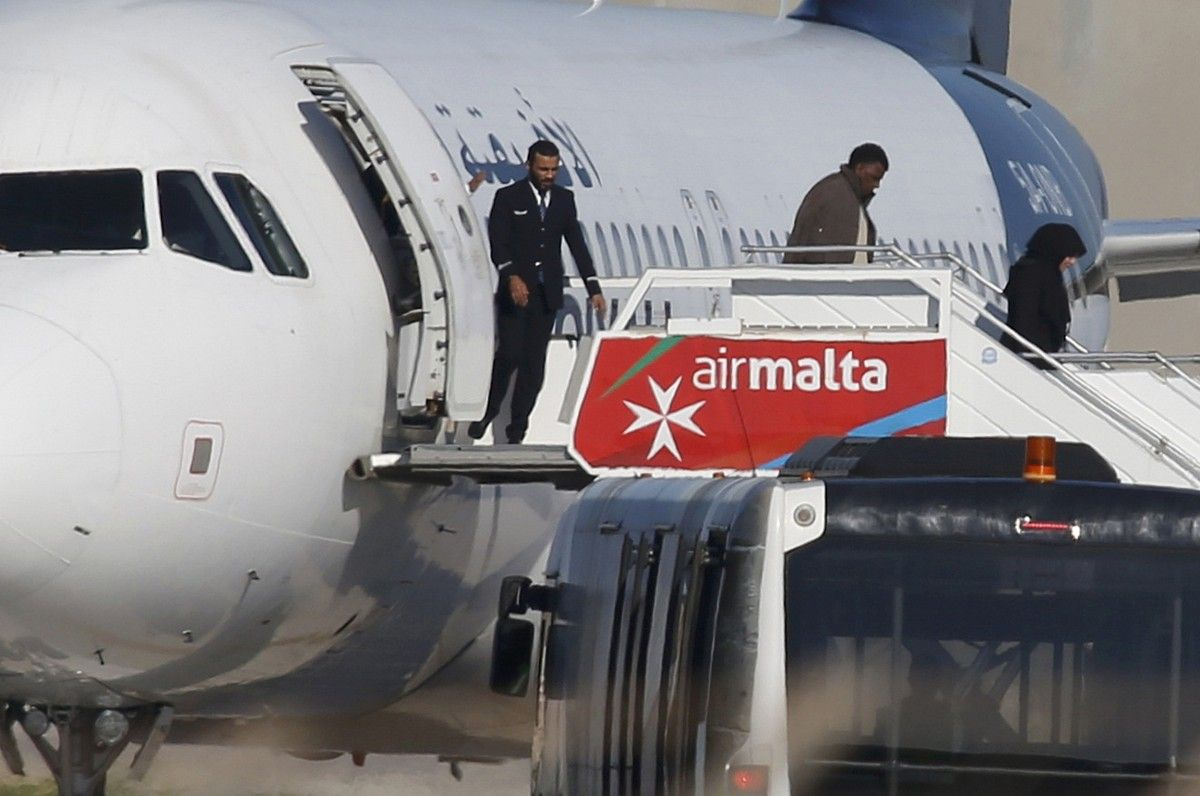 Люди выходят из захваченного ливийского самолета / REUTERS