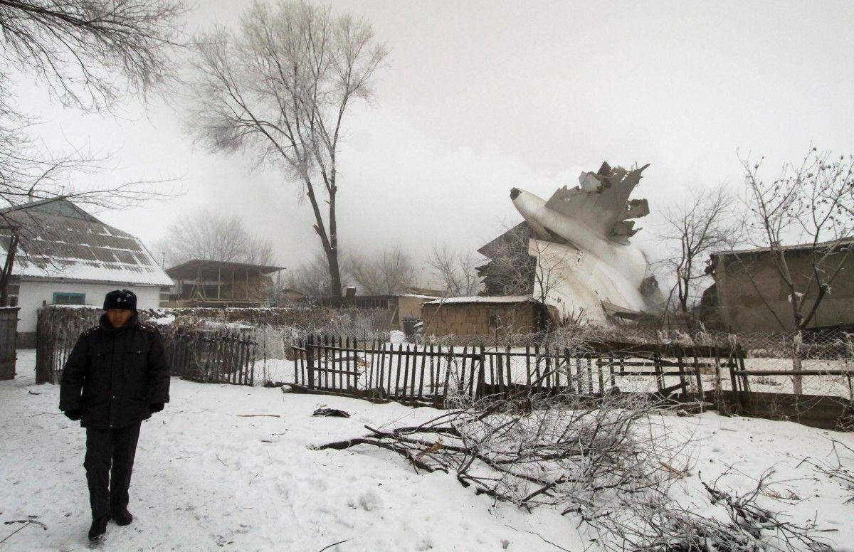 Полицейский охраняет место крушения турецкого грузового самолета недалеко от аэропорта Манас в Кыргызстане  / REUTERS