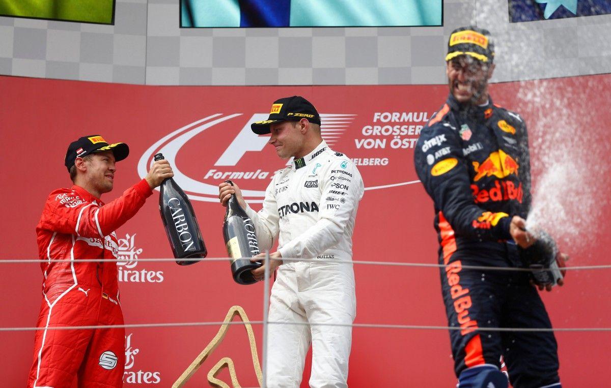 Валттери Боттас (в центре) празднует победу вместе с Себастьяном Феттелем и Даниэлем Риккардо / Reuters