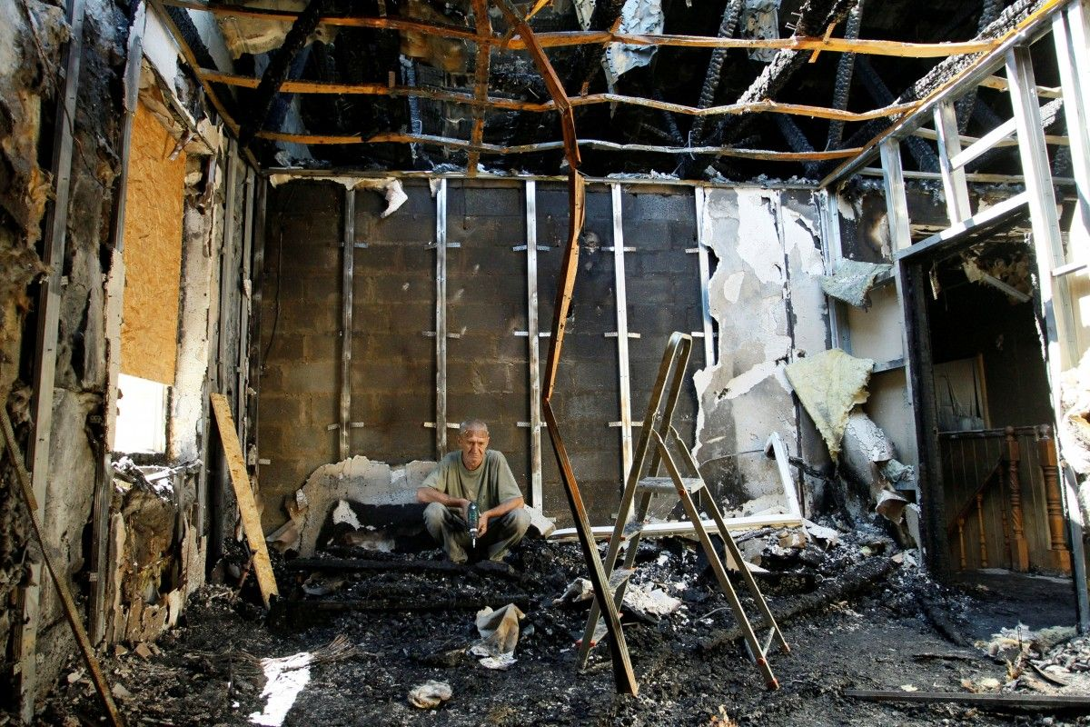 Мужчина в своем разрушенном доме в Донецке / REUTERS