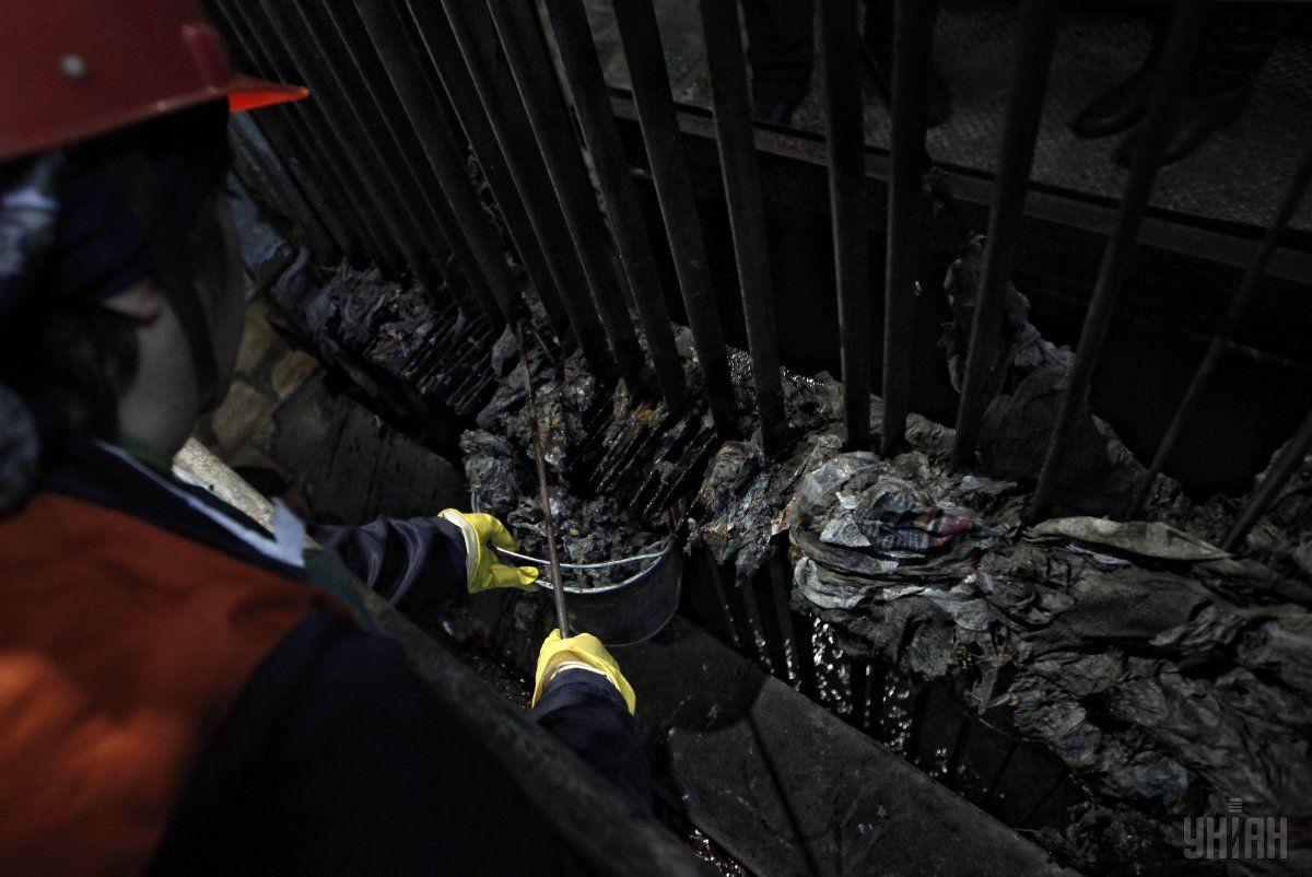 Оператор очищает остатки от мусор на насосной станции