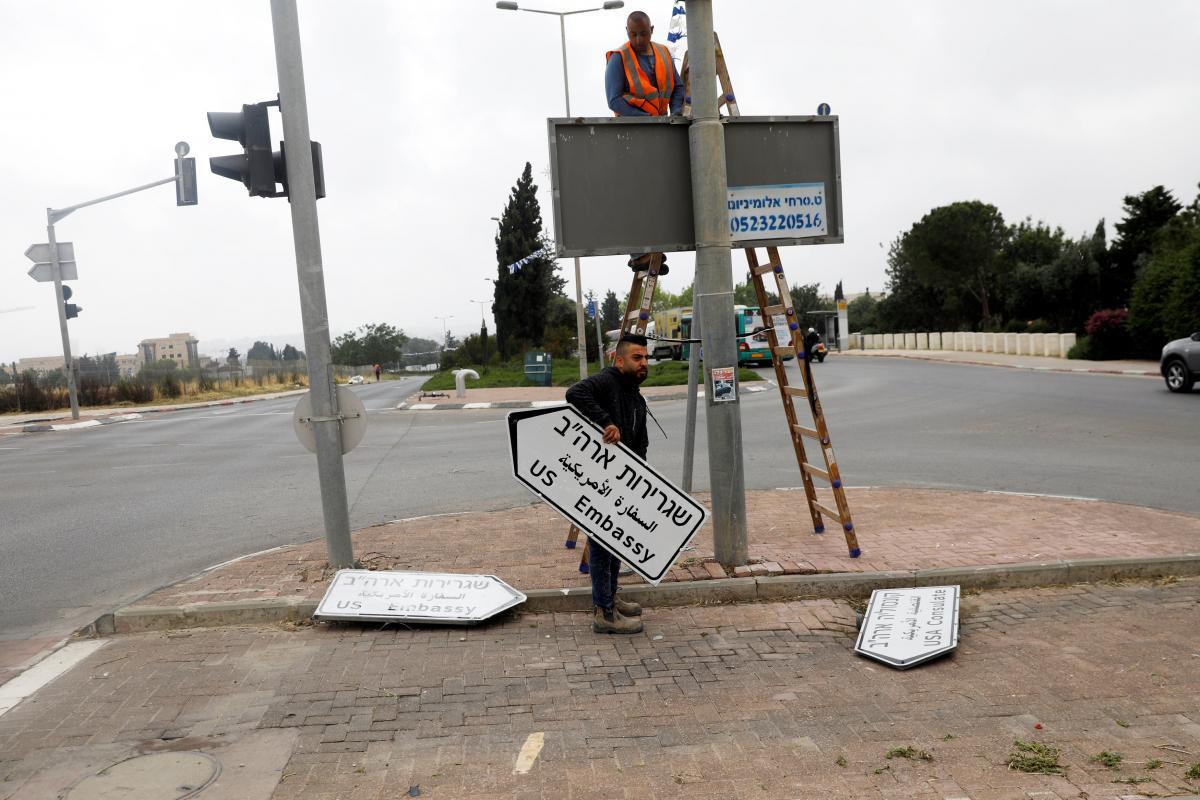 Работник держит дорожный знак, который указывает в посольство США / REUTERS