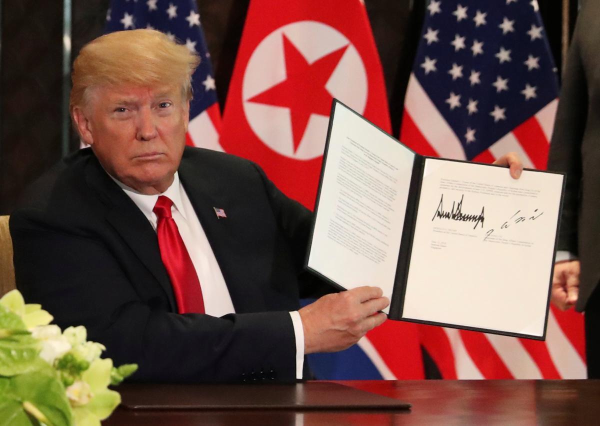 Дональд Трамп во время подписания совместного документа с Ким Чен Ыном / REUTERS