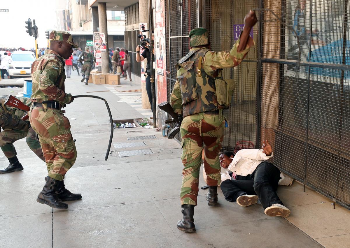 Солдаты избивают участника протестов / REUTERS