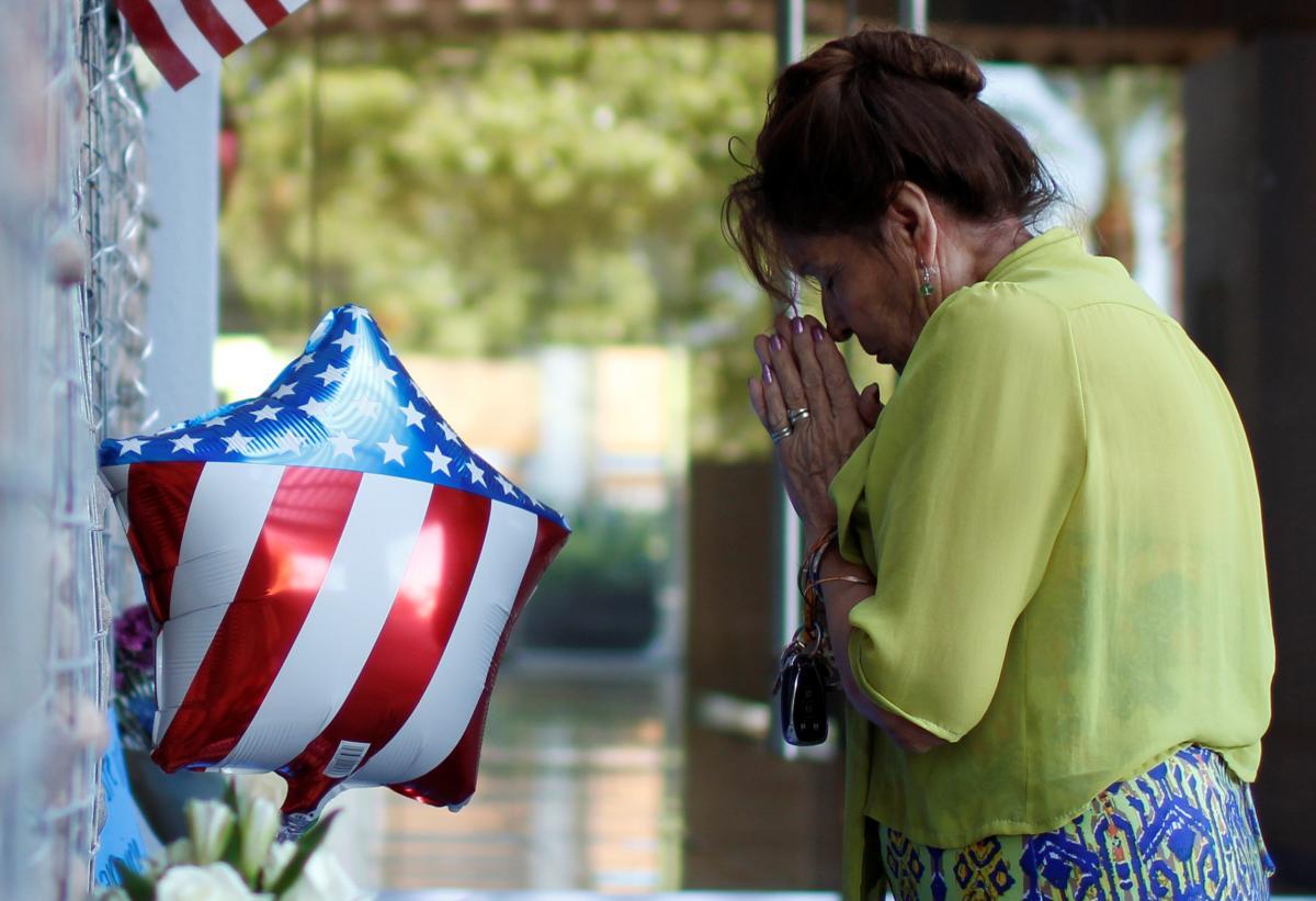 Американка молится перед мемориалом покойного сенатора США/ REUTERS
