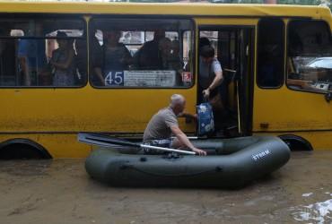 В затопленном Львове мужчина на лодке спасал людей из водяной ловушки (видео, фоторепортаж)