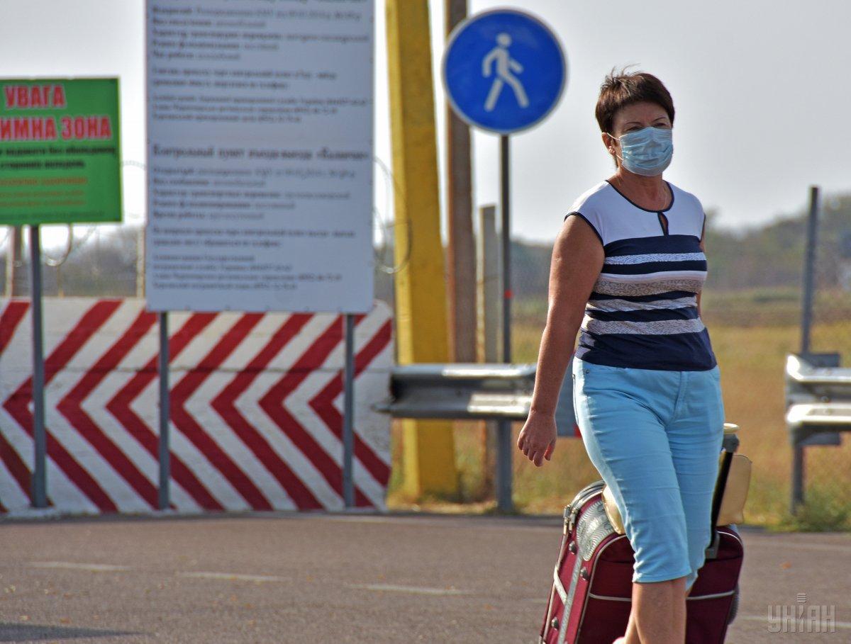 Через пункт пропуска большинство людей проходят в масках и респираторах/ фото УНІАН