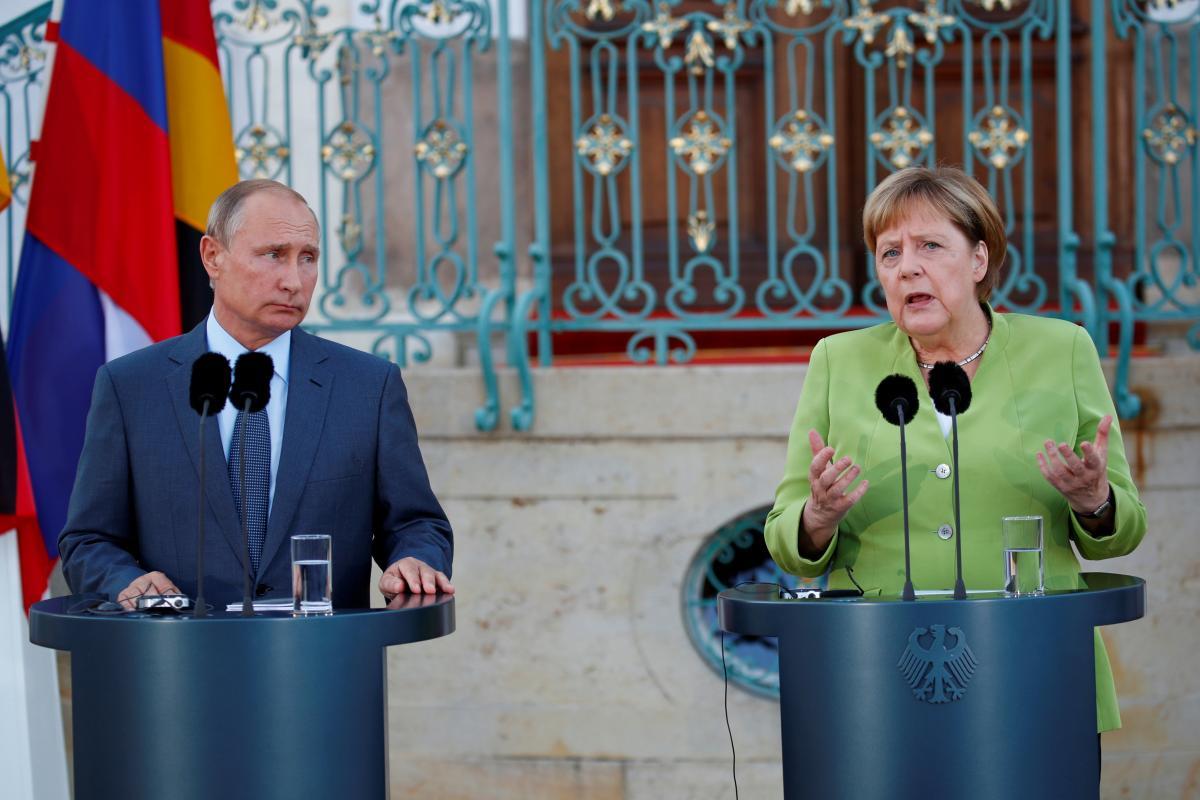 Меркель призвала Путина уменьшить численность войск РФ у границ Украины / Владимир Путин и Ангела Меркель / REUTERS