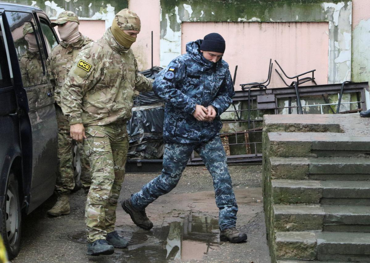 Сотрудник ФСБ конвоирует украинского моряка / фото REUTERS