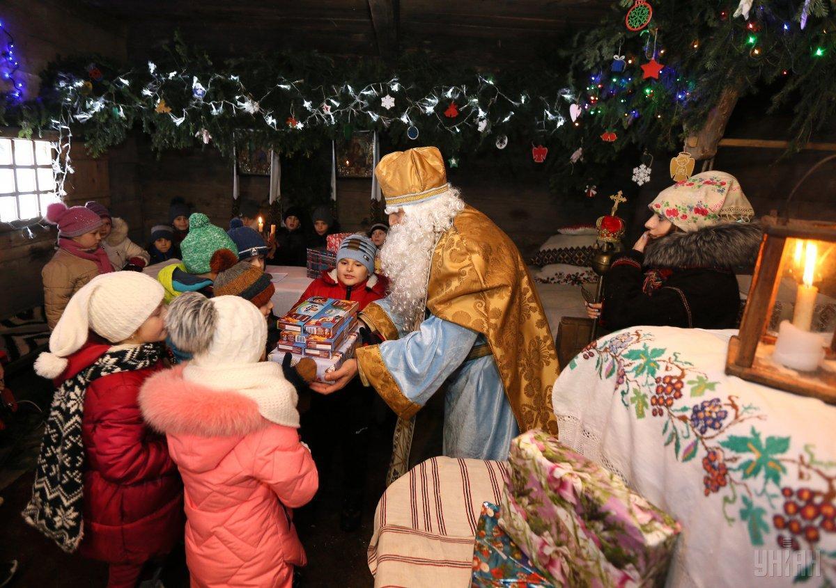 Миколай кладе дітямподарунки під подушку / фото УНІАН