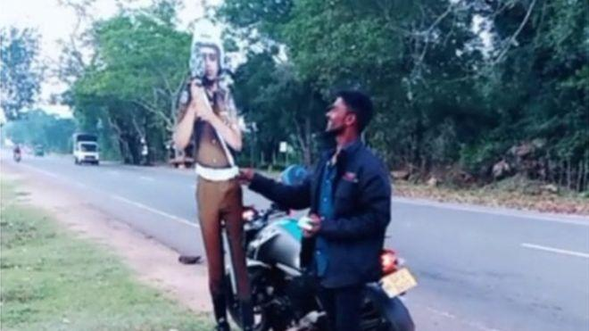 Один з хлопців під'їжджає на мотоциклі до картонної фігури поліцейського і нібито дає йому гроші \ VAVUNIYA POLICE