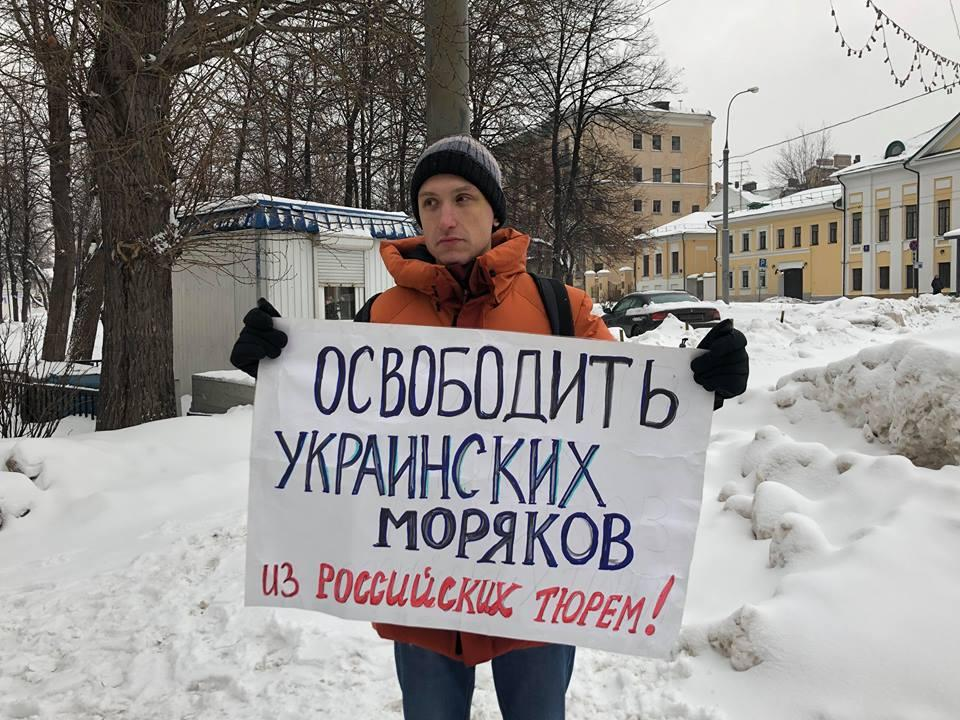 "Man holding a poster saying ""Free Ukrainian sailors from Russian prisons"" / prm.ua"