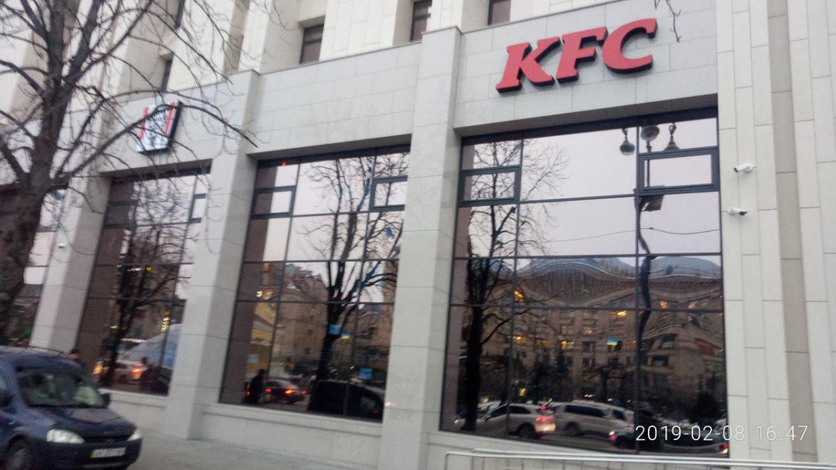 Навітринних вікнах першого поверху будівлі під вивіскою розміщено рекламний текст KFC / фото Дмитро Хилюк, УНІАН