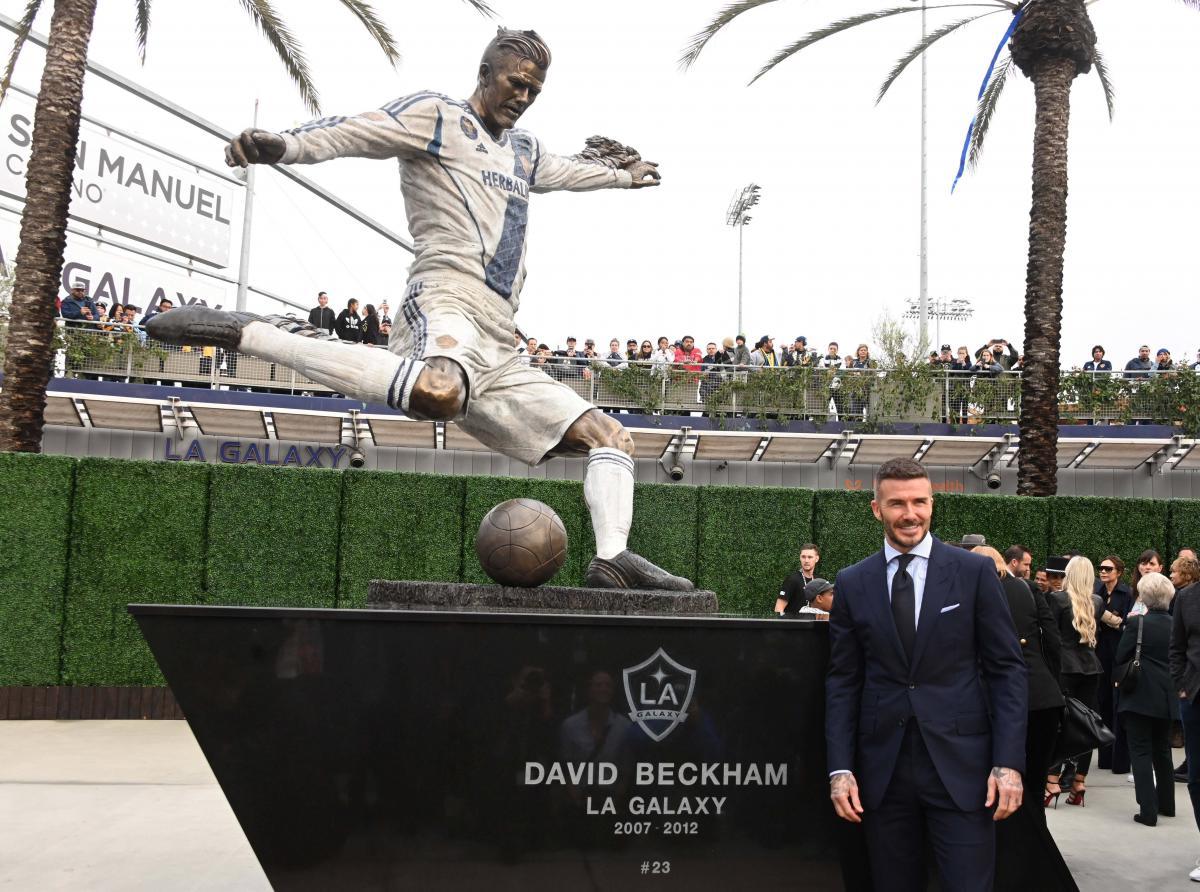 """Дэвид Бекхэм на фоне настоящей статуи возле стадиона """"Лос-Анджелес Гэлакси"""" / REUTERS"""