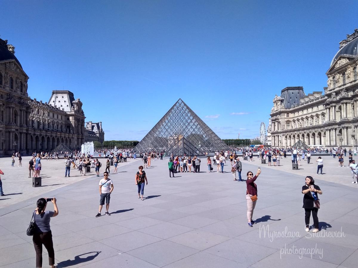 Туристи роблять фото на фоні Піраміди Лувра/ фото Myroslava Shulhevich