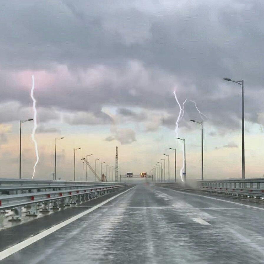 На фото видно, как в автомобильную часть моста ударили сразу две молнии / Kerchinfo