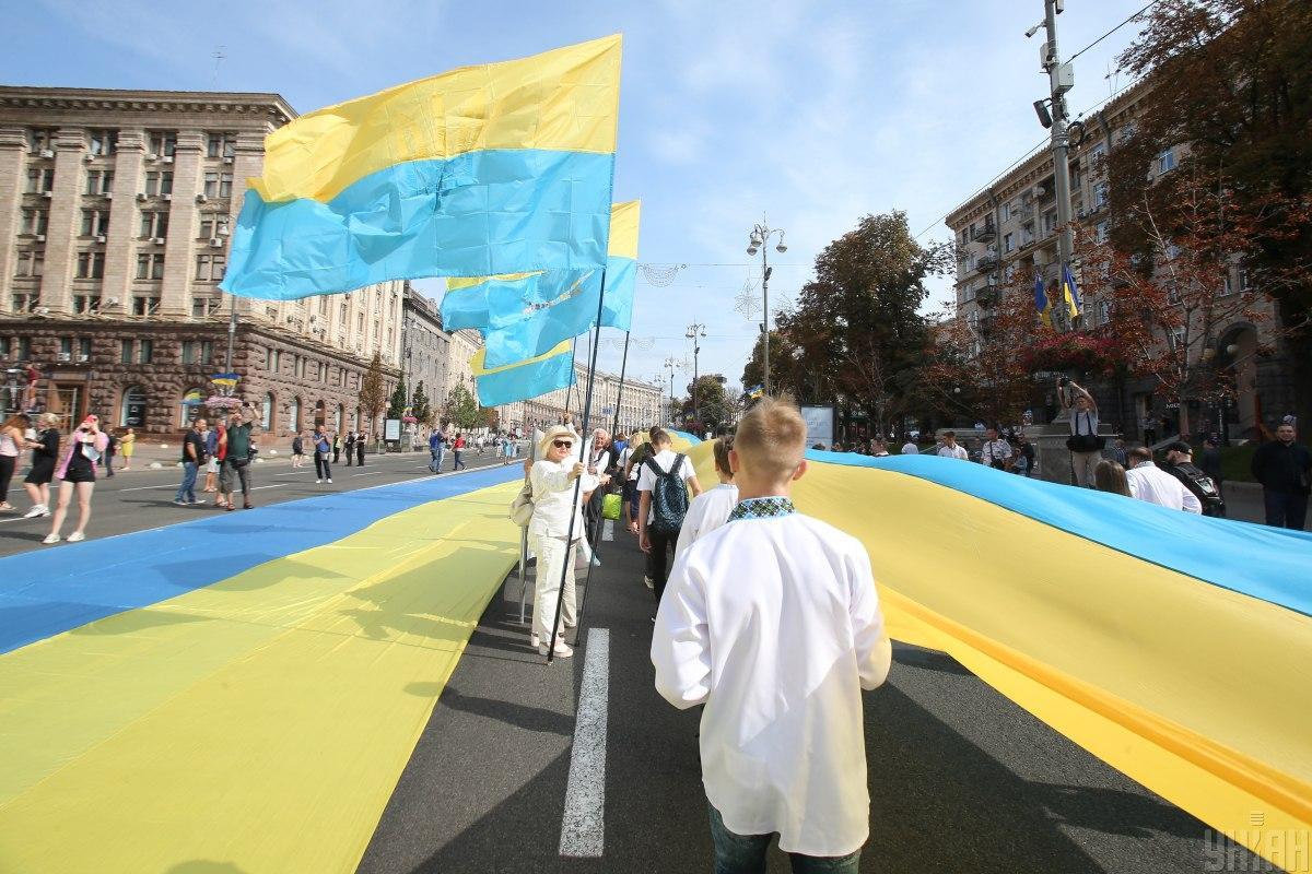 Желающие фотографировались на фоне флага / УНИАН