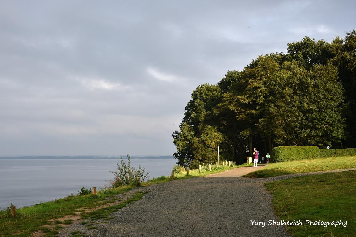 Відпочивальники гуляють узбережжям / фото Yury Shulhevich