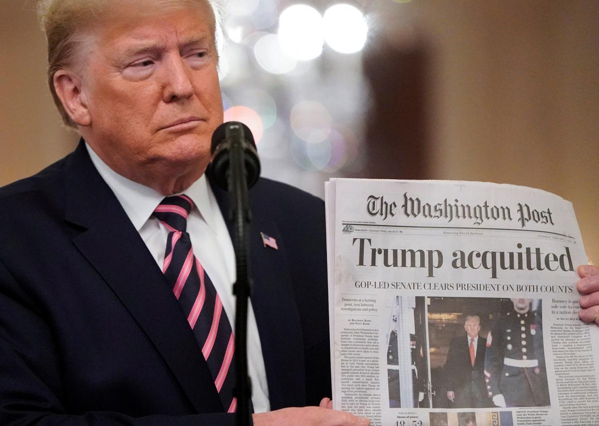 Trump is holding up a copy of The Washington Post to show its banner headline / REUTERS