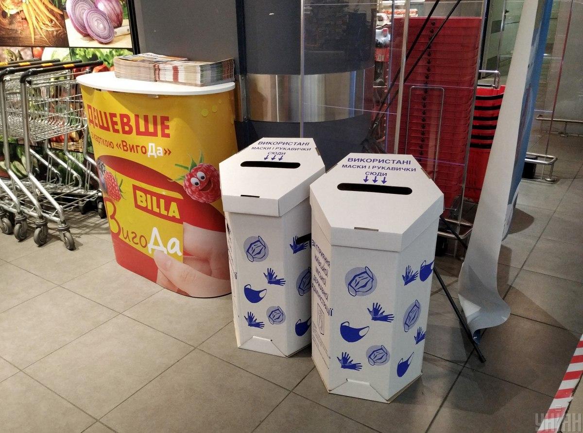 Контейнери для використаних масок на вході в один із магазинів / фото УНІАН