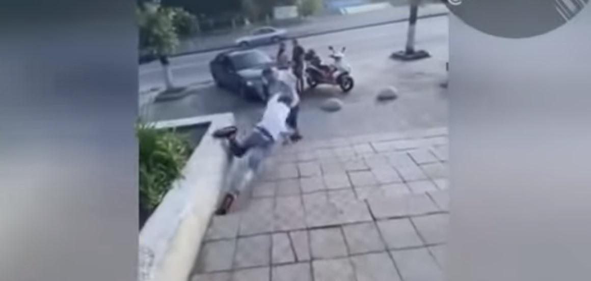 Після невдалого удару ногою в спину хлопець оступився і впав долілиць на плитку / скріншот з відео
