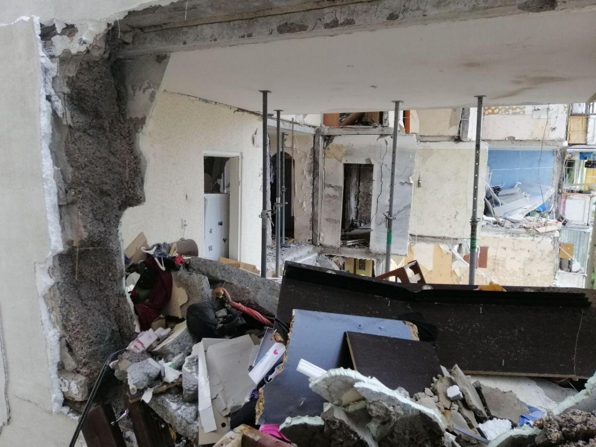 Началась «генеральная уборка» и во втором соседнем доме. Во вторник его жители выбрасывали разрушенные взрывной волной рамы, двери, заметали стекла / Фото УНИАН
