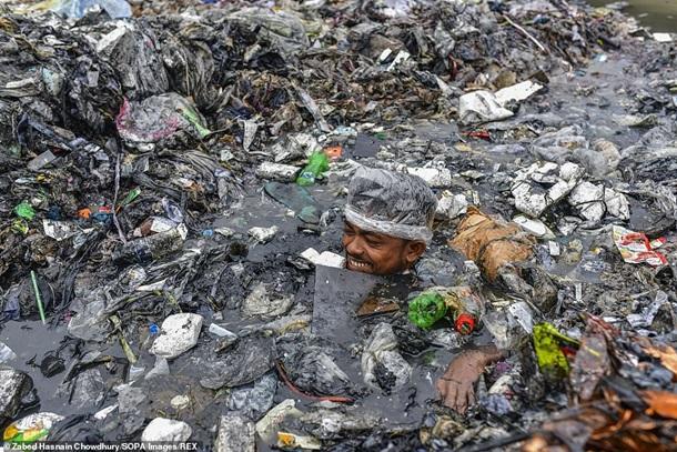 Не смотря ни на что, чистильщики рек выполняют свою работу с улыбкой/ фото Daily Mail