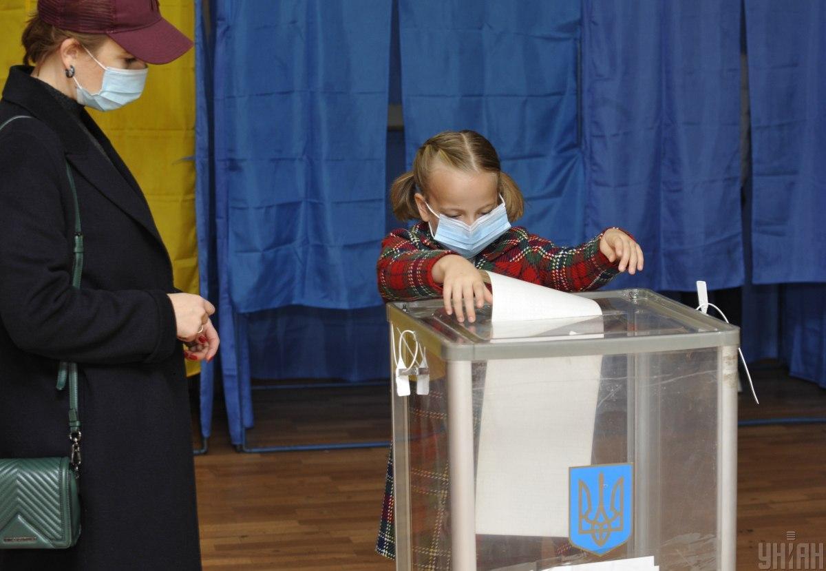 Голосовать могут только совершеннолетние украинцы, но закон не запрещает взрослым брать детей на избирательный участок / фото УНИАН