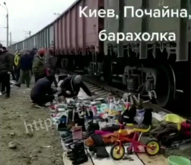 Люди продають речі, розкладені на землі на підстилках / скріншот з відео