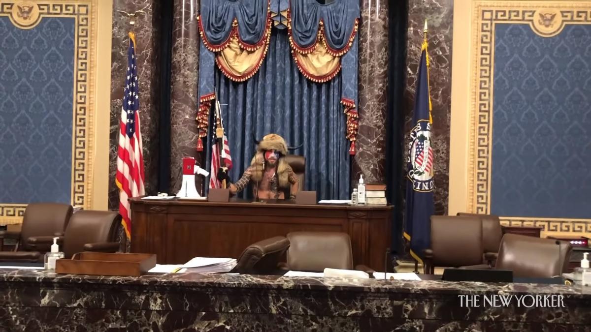 """На записи видно, что """"шаман QAnon"""" оставляет на столе спикера Сената лист с надписью: """"Это только вопрос времени, правосудие грядет""""/ скриншот из видео"""
