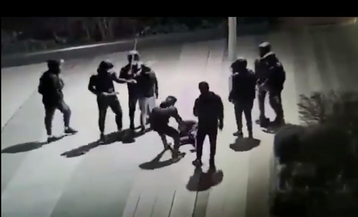 На записи видно, как лежащего на улице ребенка избивает группа из десяти человек/ скриншот из видео