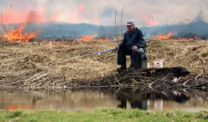 Білорус спокійно вудить рибу на тлі бурхливої пожежі
