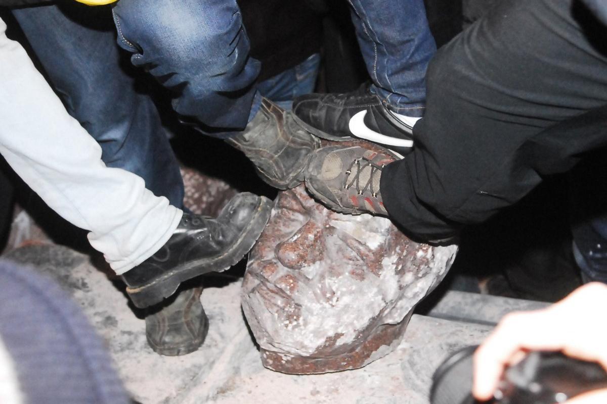 Люди б'ють ногами відбиту від пам'ятника Леніну голову на бульварі Шевченка в Києві, в неділю, 8 грудня 2013 р./ Фото - ЄвгенКолесник,УНІАН