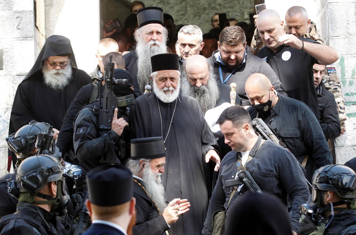Співробітники служби безпеки супроводжують патріарха Портфірія та єпископа Іоаникія / фото REUTERS