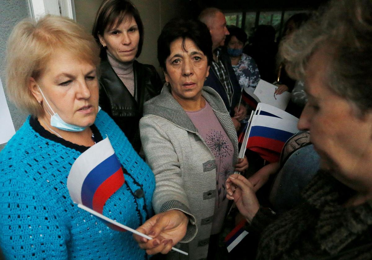 В окупованій Макіївці людям, які відправляються голосувати в Ростовську область, роздають прапорці РФ / фото REUTERS